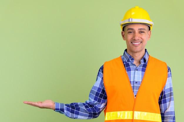 Przystojny wieloetniczny mężczyzna robotnik budowlany przed kolorową ścianą