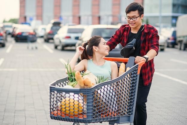 Przystojny wietnamski chłopak i ładna dziewczyna wychodzą ze sklepu i przenoszą się do samochodu. śmieszne rodzinne zakupy.