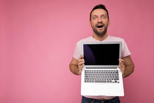 Przystojny wstrząśnięty mężczyzna trzyma laptopa patrząc na kamery w t-shirt na na białym tle różowym.