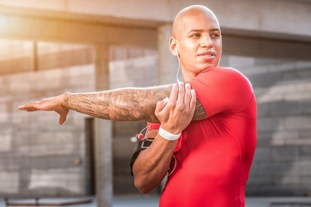 Przystojny wygląd. atrakcyjny miły mężczyzna robi ćwiczenia sportowe jednocześnie rozwijając swoje mięśnie