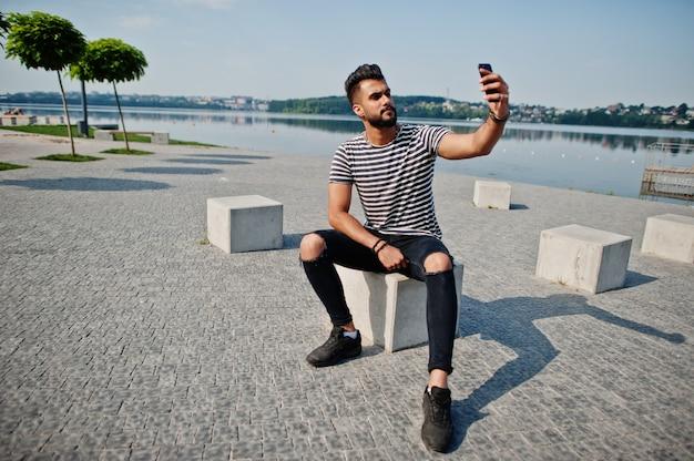 Przystojny wysoki model arabski broda mężczyzna w pasiastej koszuli postawił na zewnątrz. modny arabski facet z telefonem komórkowym.
