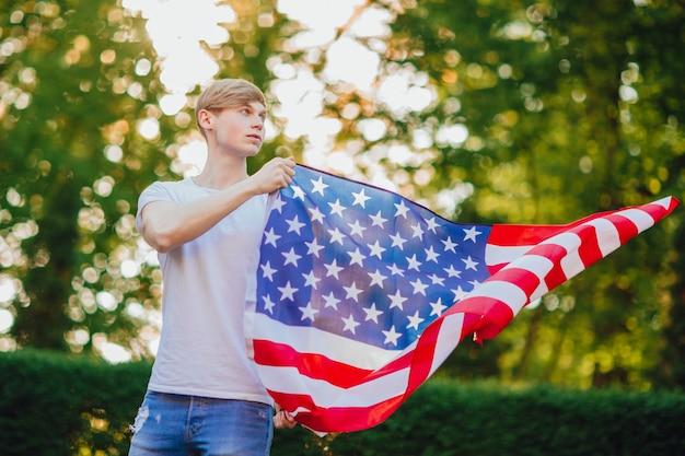Przystojny wysportowany chłopak z jasnymi włosami stoi z amerykańską flagą.