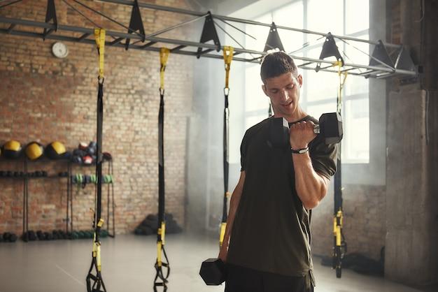 Przystojny, wysportowany mężczyzna ćwiczący z hantlami, stojący przy ścianie z cegły na siłowni