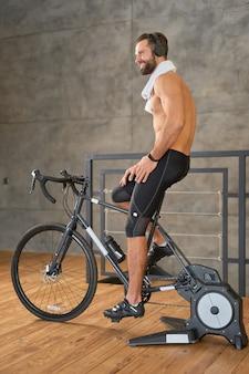 Przystojny wysportowany mężczyzna w słuchawkach, odwracając wzrok i uśmiechając się podczas treningu na rowerze stacjonarnym w pomieszczeniu