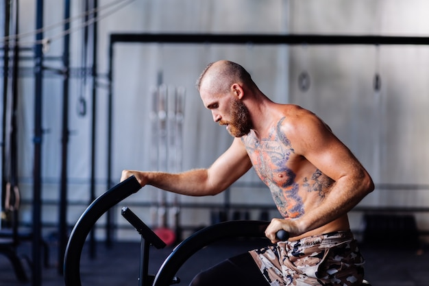 Przystojny wytatuowany siłacz w siłowni robi cardio