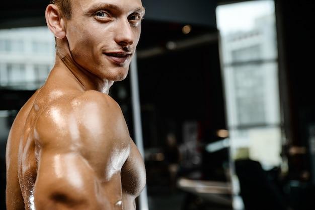 Przystojny wzorcowy młody człowiek pozuje w gym