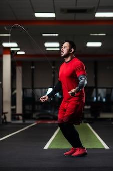 Przystojny z dużymi mięśniami skacze na linie w siłowni