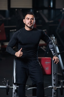 Przystojny z dużymi mięśniami w czarnych ubraniach pokazuje dobry nastrój