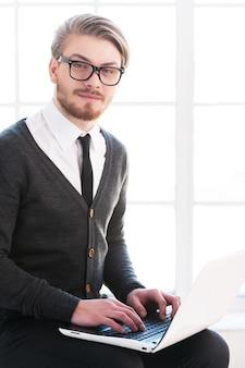 Przystojny z laptopem. przystojny młody mężczyzna pracuje na laptopie i uśmiecha się do kamery siedząc na krześle