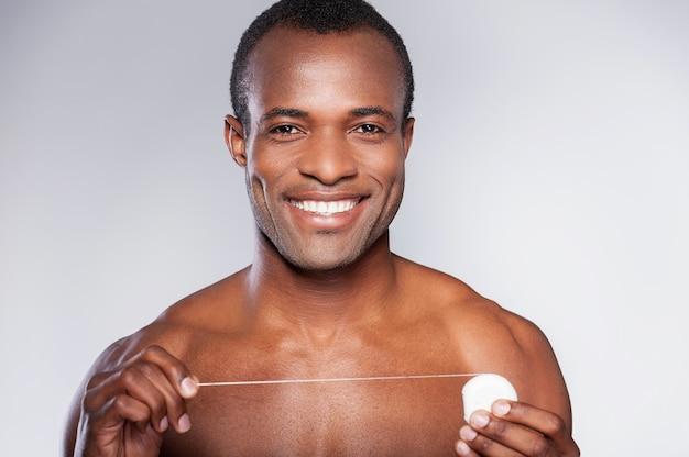 Przystojny z nicią dentystyczną. portret młodego półnagi afrykańskiego mężczyzny trzymającego nić dentystyczną i uśmiechającego się stojąc na szarym tle