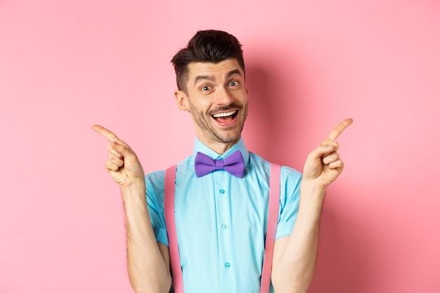 Przystojny zabawny facet wskazując palcami na bok, pokazując lewe i prawe logo i uśmiechając się, polecając dwie opcje, stojąc na różowym tle.