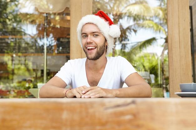 Przystojny zabawny młody człowiek udający świętego mikołaja, ubrany w czerwony kapelusz z białym futrem i uśmiechnięty wesoło, przewidujący dobrą imprezę z przyjaciółmi