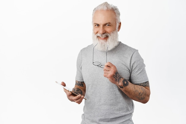 Przystojny zadowolony starszy mężczyzna trzymający cyfrowy tablet, gryzącą świątynię okularów i uśmiechnięty zadowolony, robiący zakupy online, wysyłający wiadomości w mediach społecznościowych, stojący nad białą ścianą
