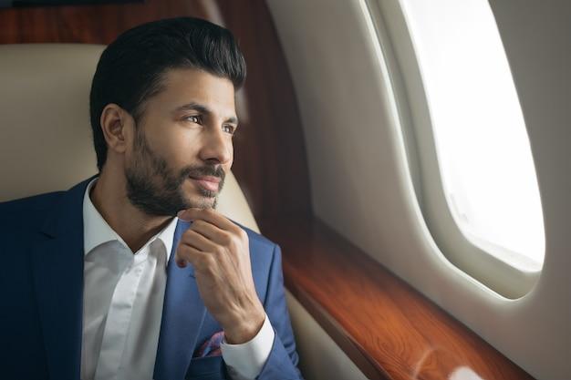 Przystojny zamyślony arabski biznesmen latający luksusowy prywatny odrzutowiec udanej koncepcji biznesowej