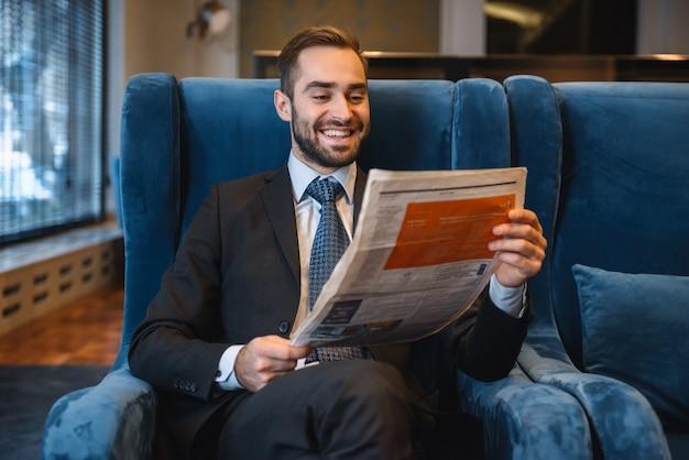 Przystojny zamyślony młody biznesmen ubrany w garnitur siedzi w holu hotelu, czytając gazetę