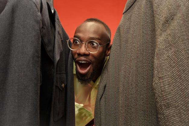 Przystojny zaskoczony mężczyzna z brodą wybiera koszulę w sklepie.