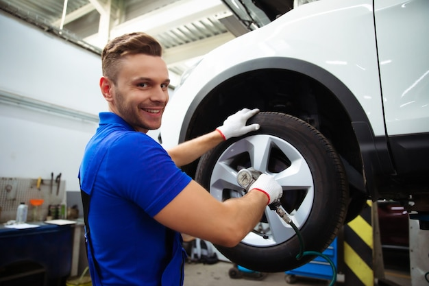 Przystojny zawodowy mechanik samochodowy zmienia koło w samochodzie lub przeprowadza wymianę opon w specjalistycznym warsztacie samochodowym