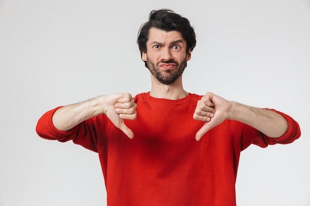 Przystojny zdenerwowany młody brodaty mężczyzna brunetka ubrana w sweter stojący na białym, kciuki w dół