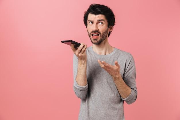 Przystojny zdezorientowany młody brodaty mężczyzna brunetka ubrana w sweter stojący nad różowym, trzymając telefon komórkowy