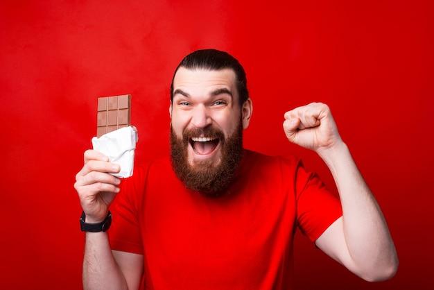 Przystojny zdumiony brodaty mężczyzna trzyma czekoladę i gestykuluje, najlepsza czekolada