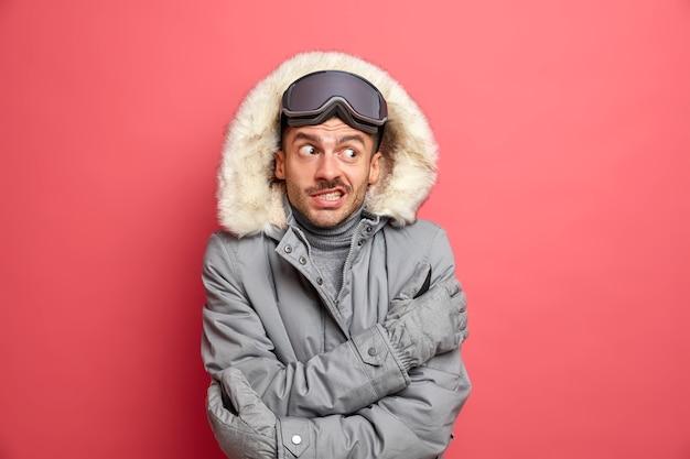 Przystojny, zdziwiony, nieogolony narciarz drży i drży podczas mroźnego mroźnego dnia, nienawidzi zimowych mrozów, nosi okulary snowboardowe i szarą kurtkę.