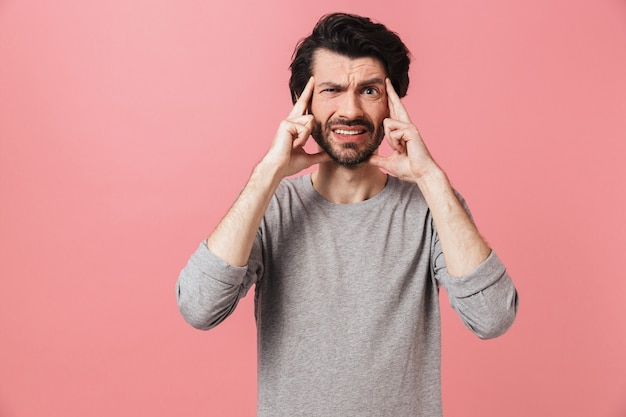 Przystojny, zmęczony, młody, brodaty brunet sobie sweter stojący na białym, cierpiącym na ból głowy