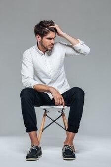 Przystojny zrelaksowany mężczyzna siedzący na krześle nad szarą ścianą