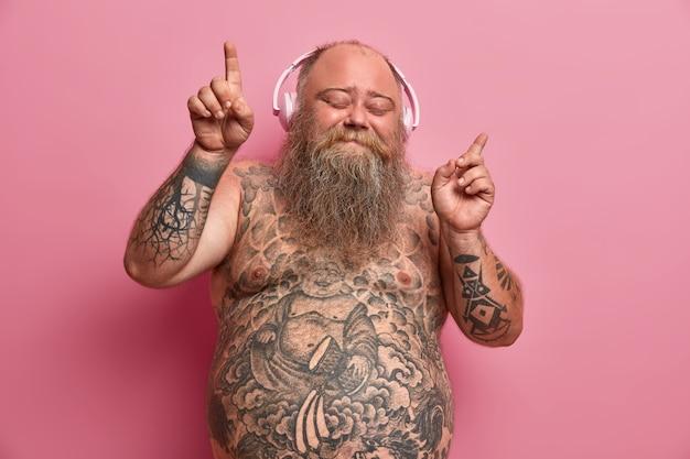 Przystojny, zrelaksowany otyły mężczyzna tańczy do muzyki w słuchawkach, cieszy się każdą piosenką, podnosi ręce i wskazuje palcami, stoi z zamkniętymi oczami, całe ciało pokryte tatuażami.