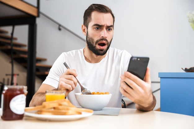 Przystojny zszokowany młody człowiek jedzący śniadanie siedząc w kuchni, trzymając telefon komórkowy