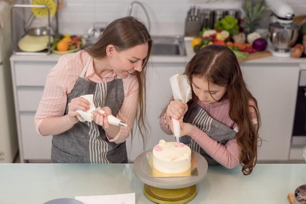 Przyszła mama i córka dekorują babeczki na kuchennym stole, bawiąc się razem jedząc świeżo upieczone ciastka