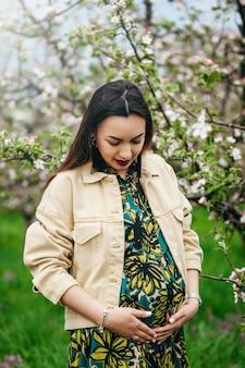 Przyszła mama stoi w ogrodzie z kwitnącymi drzewami