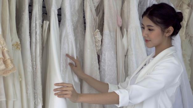 Przyszła panna młoda wybiera suknię ślubną na nadchodzącą ceremonię ślubną.