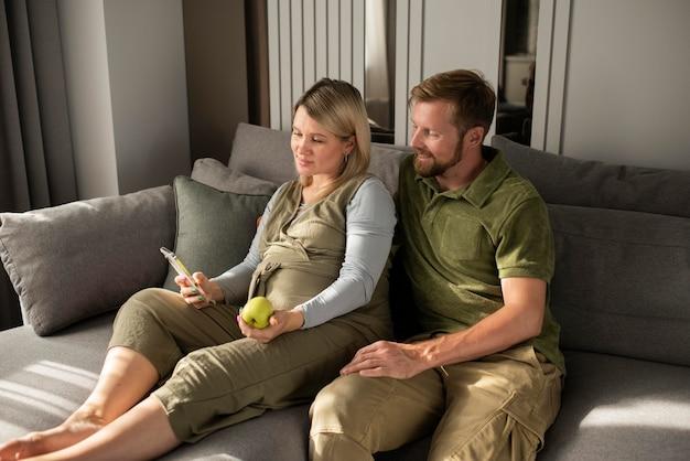 Przyszli rodzice siedzący na kanapie w średnim ujęciu