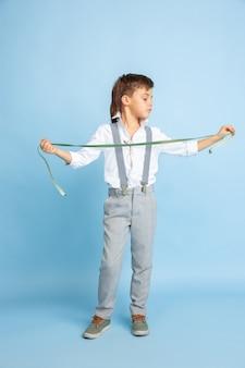 Przyszłość. mały chłopiec marzy o zawodzie krawcowej. koncepcja dzieciństwa, planowania, edukacji i marzeń. chce odnieść sukces w branży modowej i stylistycznej, atelier, szyje ubrania.