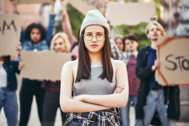 Przyszłość to kobieta, młoda kobieta w okularach, stojąca na drodze ze skrzyżowanymi