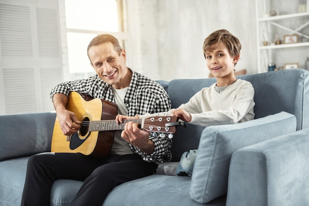 Przyszły gitarzysta. przystojny, czujny, dobrze zbudowany mężczyzna trzymający gitarę i siedzący na kanapie uczy syna gry na gitarze