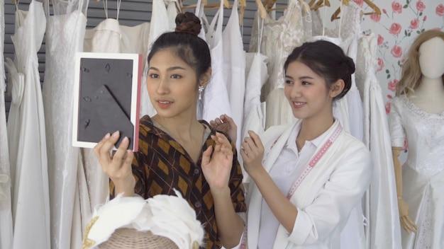 Przyszły panna młoda klient rozmawia ze sklepikarzem sklepu ślubnego