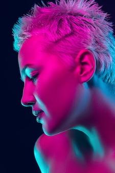 Przyszły. portret modelki w świetle neonowym na ciemnym tle studio. piękna kaukaska kobieta z modnym makijażem i zadbaną skórą. żywy styl, koncepcja piękna. ścieśniać. copyspace