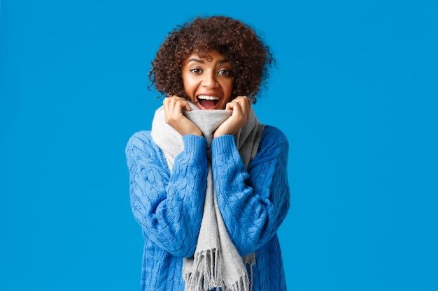 Przyszły wesołe wakacje, wreszcie śnieg i piękny zimowy sezon. wesoła optymistyczna charyzmatyczna afroamerykańska kobieta w swetrze i ciepłym szaliku, śmiejąca się i uśmiechnięta z radością, niebieska