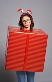 Przytłoczona kobieta stojąca zapakowana w wielki prezent gwiazdkowy