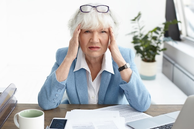 Przytłoczona, sfrustrowana, dojrzała europejska księgowa, ubrana w formalny garnitur, z bolesnym, zestresowanym wyglądem z powodu błędu w sprawozdaniu finansowym, masująca skronie, cierpiąca na ból głowy