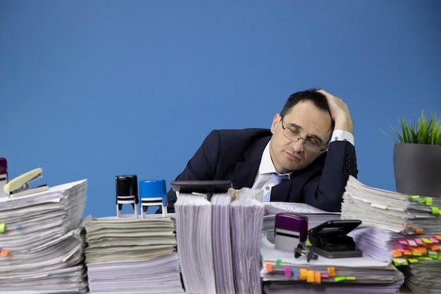 Przytłoczony biznesmen śpi przy biurku wypełnionym papierami