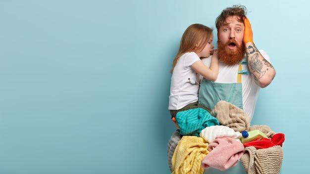 Przytłoczony, zaskoczony brodaty rudy mężczyzna z opuszczoną szczęką, trzyma rękę na głowie, nosi płaczącą córkę, czuje się zaskoczony, musi prać pranie, stoi pod niebieską ścianą z pustą przestrzenią.