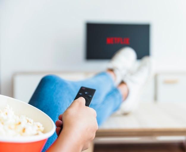 Przytnij kobietę z popcornem za pomocą pilota w telewizorze