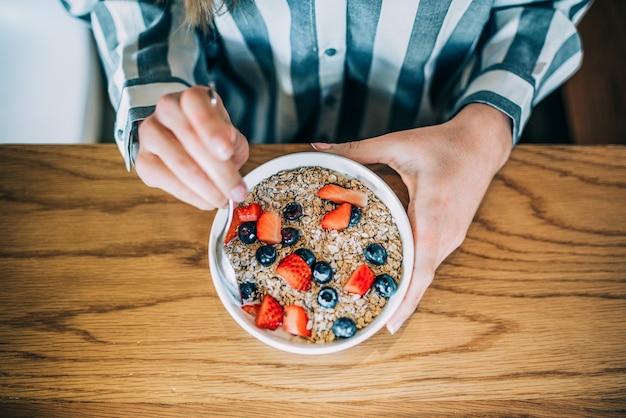 Przytnij kobiety z bliska jedzenie owsa i miski owoców na śniadanie