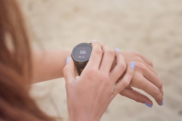 Przytnij lekkoatletkę sprawdzającą kalorie na inteligentnym zegarku