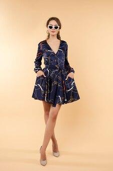 Przytnij młodej ładnej pani w ciemnoniebieskiej sukience z wzorem.