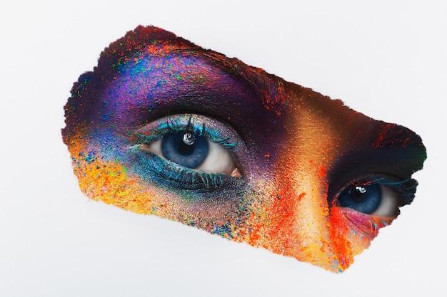 Przytnij obraz kobiecych oczu z kolorowym proszkiem makijaż patrząc. piękna modelka z kreatywnym makijażem artystycznym. streszczenie rozchlapać kolorowy makijaż. święto holi