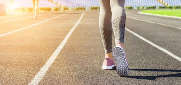 Przytnij obraz kobiecych sportowych nóg i stóp w butach do biegania na stadionie