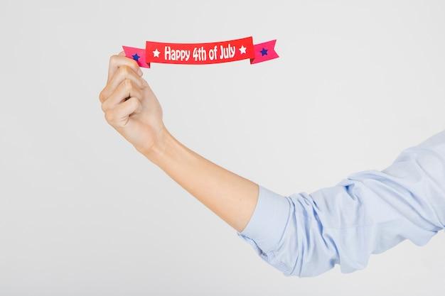 Przytnij rękę trzymając wstążkę dzień niepodległości